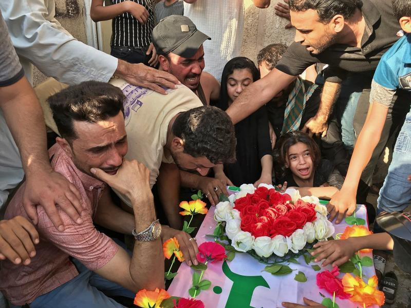 Mourners grieve at the coffin of Abu Ali al-Dabi, a fighter of the Popular Mobilization Forces during his funeral procession in Baghdad, Iraq, Monday, Aug. 26, 2019. Two unidentified drones killed two Iraqi members of an Iran-backed paramilitary force on Sunday, the group said in a statement, saying the attack took place in Iraq near the border with Syria. (AP Photo/Ali Abdul Hassan)