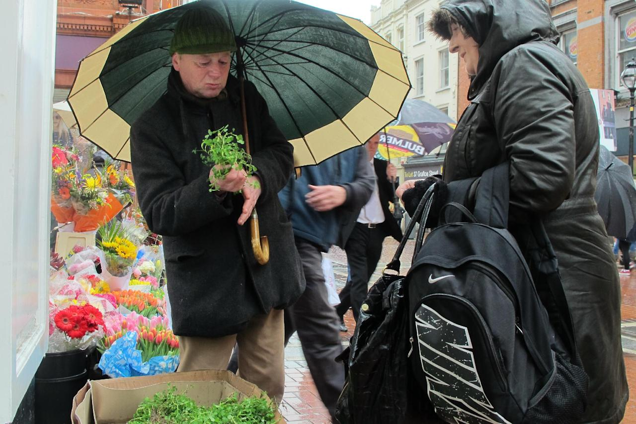 Flower seller Jimmi Lee, 55, sells a sprig of shamrock to shopper Catherine Fahy, 45, on Dublin's main shopping boulevard Friday, March 16, 2012. Dublin is getting ready for its annual St. Patrick's Day parade on upcoming Saturday and is expected to attract a half-million onlookers, many of them wearing a corsage of shamrock, the lucky symbol of Ireland. (AP Photo/Shawn Pogatchnik)