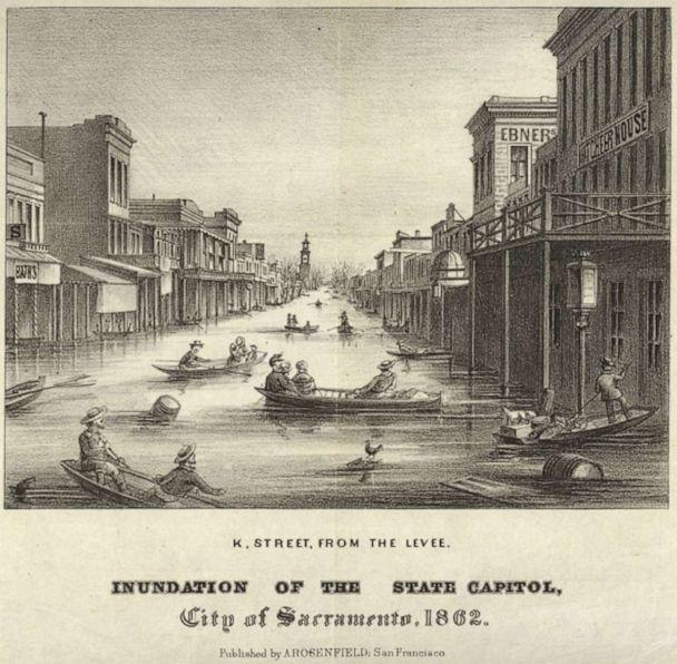 PHOTO: The inundation of the city of Sacramento during great flood of 1862 is depicted in an illustration, with  flotsam, row boats, and skiffs floating on a crowded flooded street. (California State Library, California History Room)