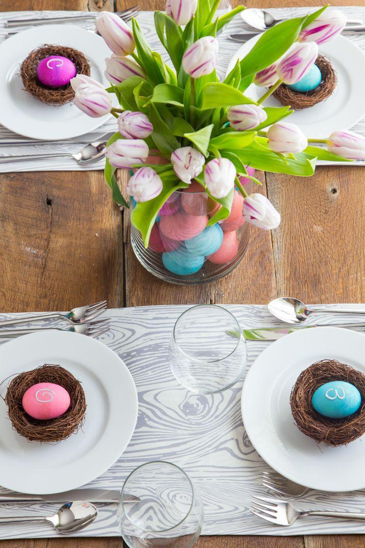 "<p>You put all that work into <a href=""https://www.countryliving.com/diy-crafts/how-to/g1282/easter-egg-decorating-ideas/"" rel=""nofollow noopener"" target=""_blank"" data-ylk=""slk:dyeing Easter eggs"" class=""link rapid-noclick-resp"">dyeing Easter eggs</a>. Why not add them to your Easter table for a super-simple setting? Here, they add color to a flower arrangement in a double-walled vase, not to mention mark each spot with a monogram sticker.</p><p><strong>Get the tutorial at <a href=""https://jellytoastblog.com/easter-egg-table-setting/"" rel=""nofollow noopener"" target=""_blank"" data-ylk=""slk:Jelly Toast"" class=""link rapid-noclick-resp"">Jelly Toast</a>.</strong></p><p><a class=""link rapid-noclick-resp"" href=""https://www.amazon.com/PRETYZOOM-Artificial-Rattan-Easter-Playset/dp/B085B2RGFJ/ref=sr_1_2?tag=syn-yahoo-20&ascsubtag=%5Bartid%7C10050.g.1652%5Bsrc%7Cyahoo-us"" rel=""nofollow noopener"" target=""_blank"" data-ylk=""slk:SHOP FAUX NESTS"">SHOP FAUX NESTS</a></p>"