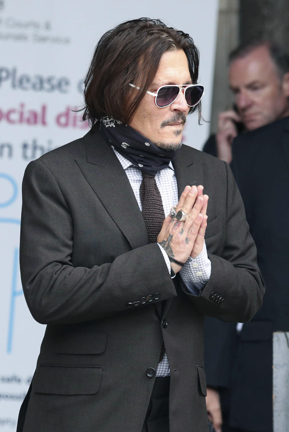 "Actor Johnny Depp gestures as he arrives at the High Court to give evidence in his libel case, in London, Wednesday July 15, 2020. Depp is suing News Group Newspapers, publisher of The Sun, and the paper's executive editor, Dan Wootton, over an April 2018 article that called him a ""wife-beater."" The Sun's defense relies on a total of 14 allegations by Amber Heard of Depp's violence. He strongly denies all of them. ( Jonathan Brady/PA via AP)"