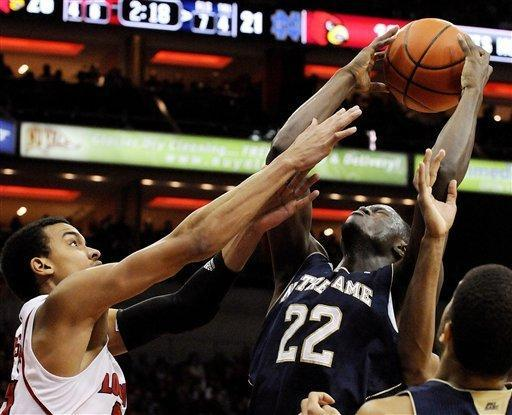 Notre Dame's Jerian Grant, right, goes up for a shot over Louisville's Jared Swopshire during the first half of their NCAA college basketball game, Saturday, Jan. 7, 2012 in Louisville, Ky. (AP Photo/Timothy D. Easley)
