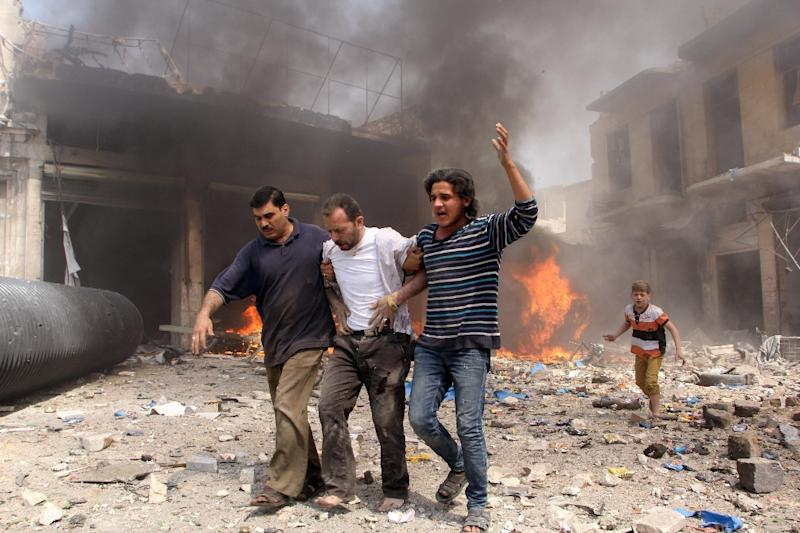 Syrian men help an injured person following a reported barrel bomb attack by Syrian government forces that hit an open market in the northern city of Aleppo on June 3, 2015 (AFP Photo/Karam Al-Masri)