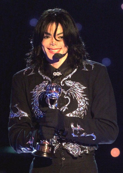 """FILE - In this May 10, 2000 file photo, pop star Michael Jackson gestures to spectators as he holds the """"Millennium Award"""" which was awarded to him at the 2000 World Music Awards ceremony in Monaco. A Los Angeles jury in a lawsuit filed by Jackson's mother against concert promoter AEG Live heard testimony Thursday, Aug. 1, 2013, from Michael La Perruque, the singer's former security chief about his concerns that the entertainer might overdose on prescription medications in the early 2000s. (AP Photo/Lionel Cironneau, file)"""