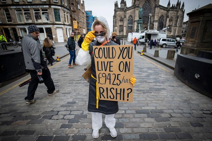 A demonstrator protests about the UK Government sick pay allowance of £94 per week for freelance and self employed workers during the coronavirus outbreak (PA)