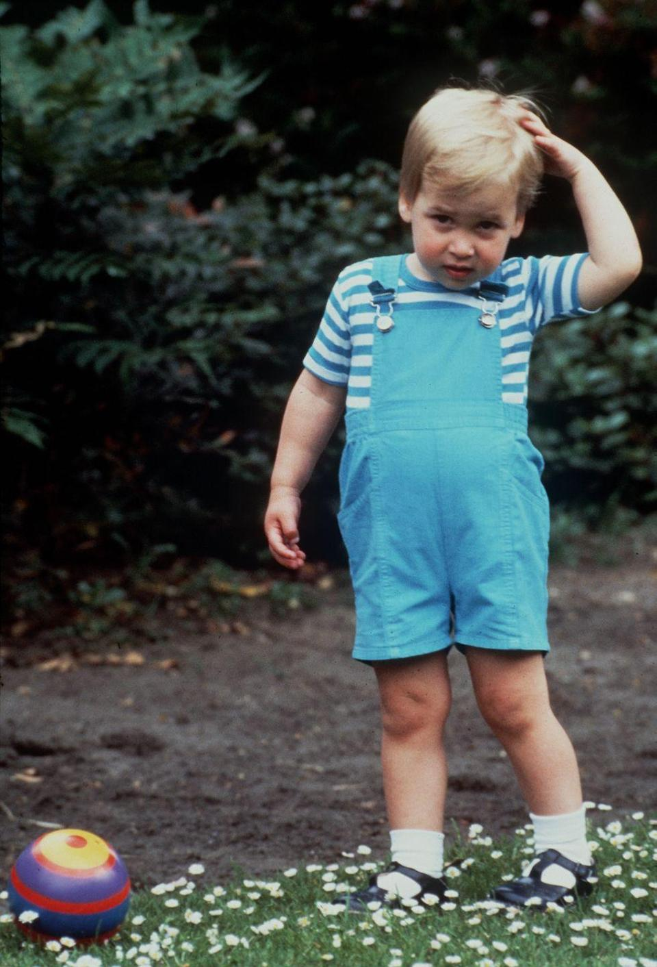 <p>Prince William looked adorable in turquoise overalls and a matching striped tee. He was photographed at his home, Kensington Palace. </p>