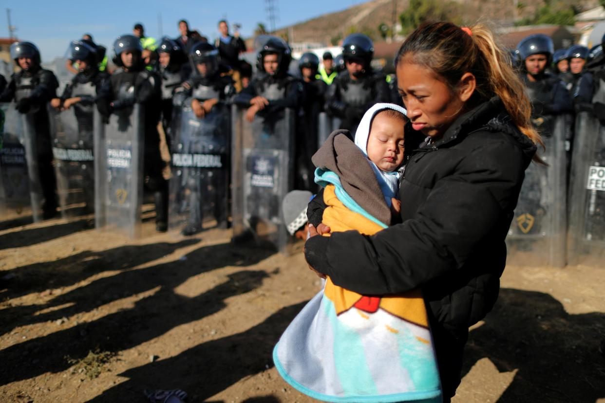 Rosa Villa, 30, and her five-month-old son Esteban from Honduras, part of a caravan of thousands traveling from Central America en route to the United States, are pushed back from the border wall between the U.S and Mexico by Mexican police in Tijuana, Mexico November 25, 2018. (Photo: Lucy Nicholson/Reuters)