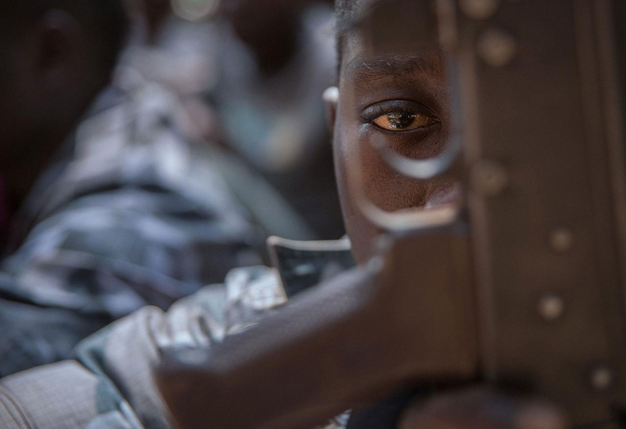 <p>A newly released child soldier looks through a rifle trigger guard during a release ceremony for child soldiers in Yambio, South Sudan on Feb. 7, 2018. (Photo: Stefanie Glinski/AFP/Getty Images) </p>