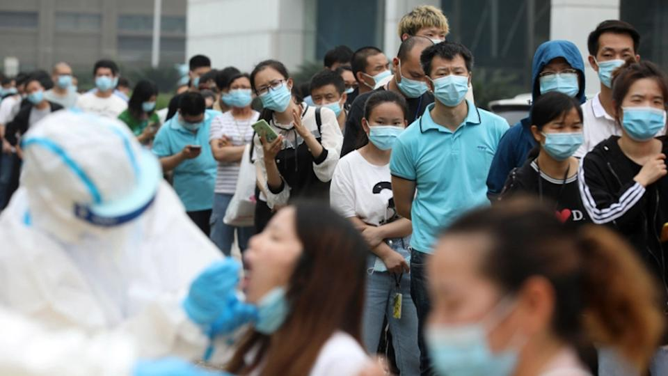 A crowd of people in China are seen wearing masks to protect from coronavirus.