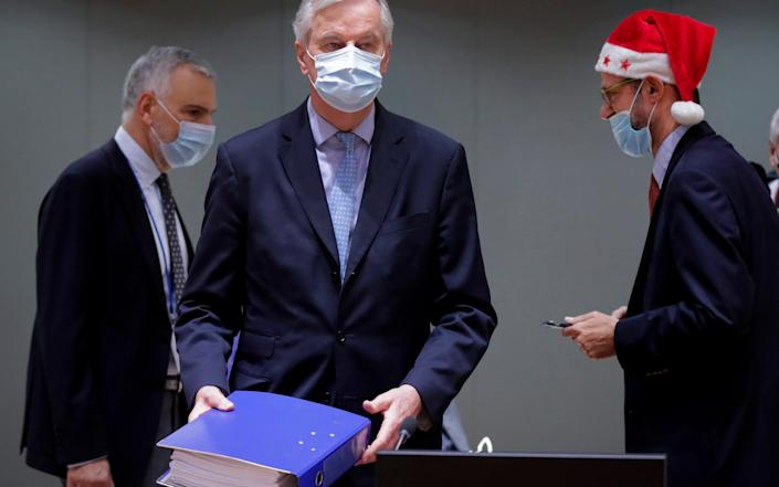 A collegue wears a Christmas hat as European Union chief negotiator Michel Barnier, center, carries a binder of the Brexit trade deal during a special meeting of Coreper, at the European Council building in Brussels - Oliver Hoslet/Pool via AP