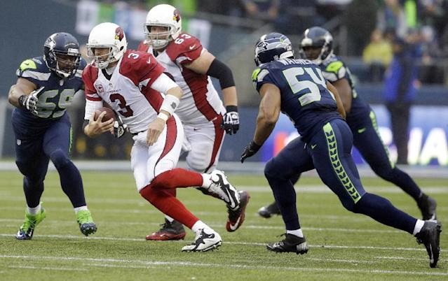 Arizona Cardinals quarterback Carson Palmer (3) keeps the ball as Seattle Seahawks defensive tackle Clinton McDonald (69) moves in at left, in the second half of an NFL football game, Sunday, Dec. 22, 2013, in Seattle. (AP Photo/Elaine Thompson)