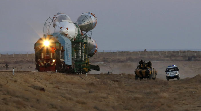Russian police guard the Russia's booster rocket Soyuz-FG with the space capsule Soyuz TMA-11M that will carry new crew to the International Space Station (ISS) as the rocket is transported from hangar to the launch pad at the Russian leased Baikonur cosmodrome, Kazakhstan, Tuesday, Nov. 5, 2013. The rocket is scheduled to blast off on Thursday, Nov.7. (AP Photo/Dmitry Lovetsky)