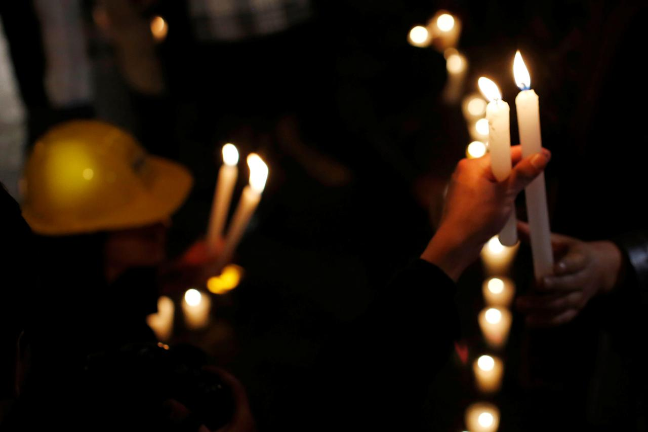 An earthquake victim holds a candle to mark the four-month anniversary of the September 19 quake in Mexico City, Mexico January 19, 2018. REUTERS/Carlos Jasso
