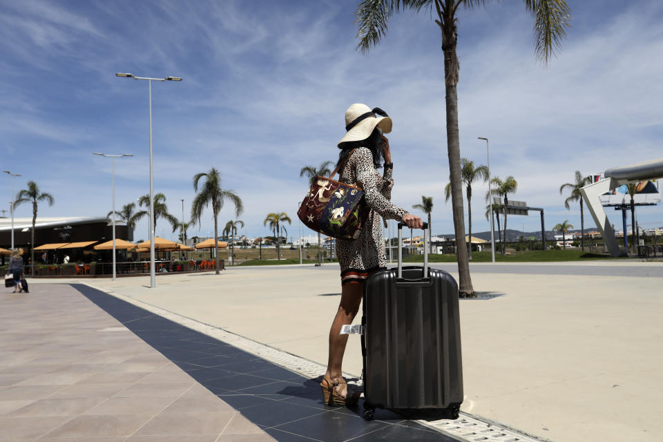 FILE - In this Monday, May 17, 2021 file photo, a passenger of a flight arriving at Faro leaves the airport, outside Faro, in Portugal's southern Algarve region. For Europe's battered tourism industry, fresh virus outbreaks and chaos and confusion over travel rules are contributing to another cruel summer. (AP Photo/Ana Brigida, File)