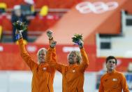 Winner Michel Mulder of the Netherlands (C), his twin brother second-placed Ronald Mulder (L), and their compatriot third-placed Jan Smeekens celebrate during the flower ceremony for the men's 500 metres speed skating race at the Adler Arena during the 2014 Sochi Winter Olympics February 10, 2014. REUTERS/Issei Kato (RUSSIA - Tags: OLYMPICS SPORT SPEED SKATING)