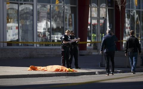 A tarp covers an unidentified body on Yonge St. at Finch Avenue - Credit: Cole Burston/Getty Images