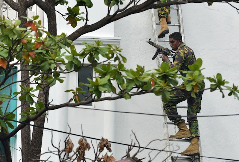 Special task force personnel climb a ladder outside a house during the raid. Source: Getty Images