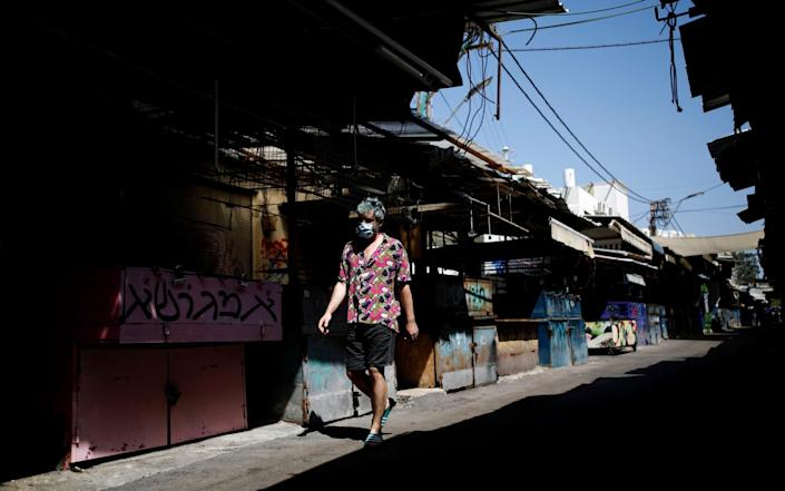An Israeli man walks in a closed market as Israel imposes a second nationwide coronavirus disease - Corinna Kern/Reuters