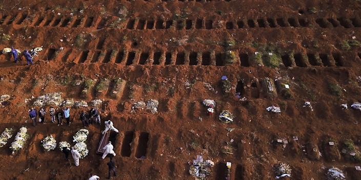 Gravediggers bury the coffin of a person who died from COVID-19 in Sao Paulo, Brazil, May 22, 2020.