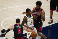 Indiana Pacers guard Edmond Sumner (5) loses the ball as he drives between Chicago Bulls guard Zach LaVine (8) and forward Thaddeus Young (21) during the first half of an NBA basketball game in Indianapolis, Tuesday, April 6, 2021. (AP Photo/Michael Conroy)