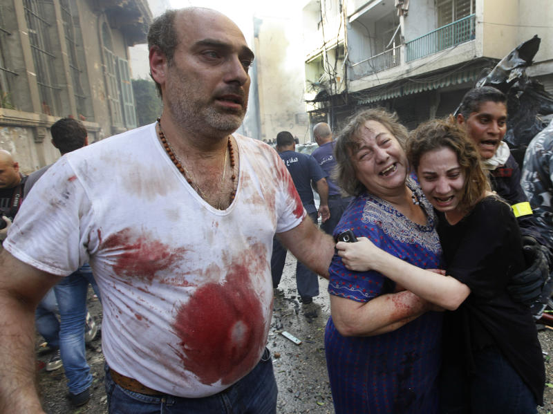Injured Lebanese leave the scene of an explosion in the mostly Christian neighborhood of Achrafiyeh, Beirut, Lebanon, Friday Oct. 19, 2012. Lebanese Red Cross and security officials say a car bomb in east Beirut has killed at least eight people and wounded dozens in the worst blast the city has seen in years, coming at a time when Lebanon has seen a rise in tension and eruptions of clashes stemming from the civil war in neighboring Syria. (AP Photo/Hussein Malla)