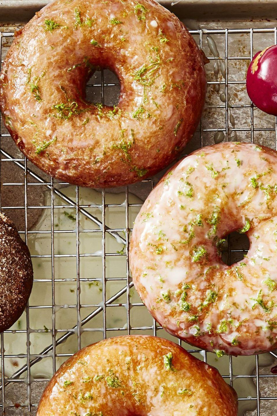 """<p>These sweet and tangy glazed donuts give you the flavor of summer, right around the corner.</p><p><em><a href=""""https://www.goodhousekeeping.com/food-recipes/a48182/coconut-lime-donuts-recipe/"""" rel=""""nofollow noopener"""" target=""""_blank"""" data-ylk=""""slk:Get the recipe for Coconut-Lime Donuts »"""" class=""""link rapid-noclick-resp"""">Get the recipe for Coconut-Lime Donuts »</a></em></p>"""
