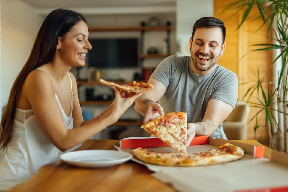 Pizza for breakfast? Why not! Cheerful couple in pajamas eating pizza at home, portrait.