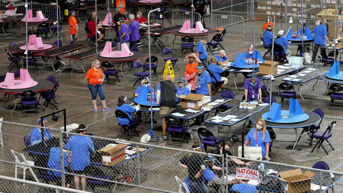 Several dozen people wearing red, blue or purple shirts with lanyards around their necks stand or sit at round tables with blue or pink vote-counting materials on them in a large room penned in by chain-link fencing.