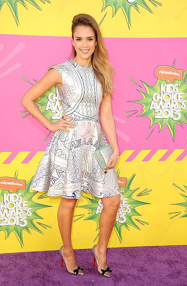 Jessica Alba popped a pose in a printed fit-and-flare dress, sideswept tresses, and sparkling bow-adorned pumps.