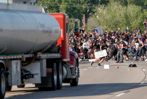 Protesters scatter as a tanker truck drives towards them on 35W highway during a demonstration against police violence following the killing of George Floyd (REUTERS)