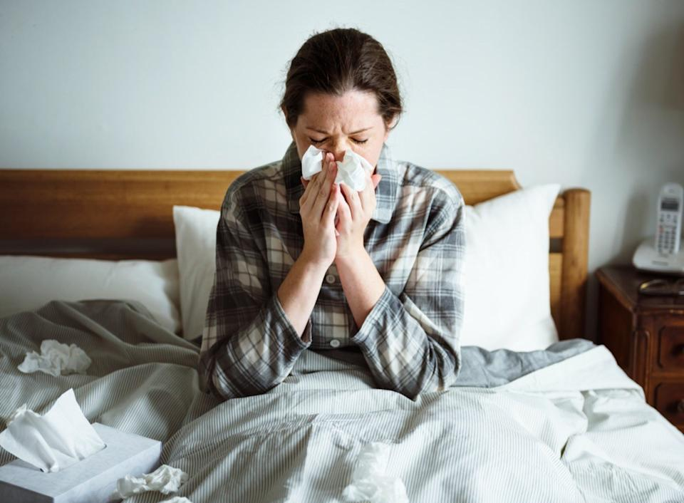 A woman suffering from flu in bed