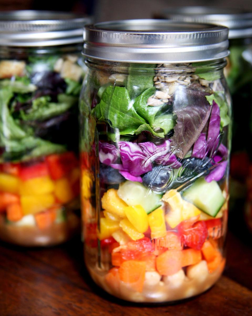 <p>Go for the quart-size jars with wide-mouth lids since these are easier to fill and eat out of. Use this system only if you can keep the jars upright. This method keeps salads fresh for five days. </p> <ol> <li><strong>Start with salad dressing.</strong> Since you keep the jar upright, the salad dressing will stay separated from your veggies. This is great if you don't want to pack a separate container for dressing. </li> <li><strong>Veggies are next.</strong> Start with harder veggies like carrots, radishes, onions, and chickpeas that will taste lovely mingling with the dressing. Then go for anything else like bell peppers, chopped cukes, and cherry tomatoes. </li> <li><strong>Layer up the greens.</strong> This should take up at least half the jar. As mentioned earlier, go for packaged greens to save time, or if you're using your own, make sure they're dry.</li> <li><strong>Protein last.</strong> Sprinkle sautéed tofu, marinated tempeh, grilled chicken, or cubed or shredded cheese on top. These will help push the lighter-weight greens down, so you add even more to your jar. You can also add avocado, nuts or seeds, and dried fruit.</li> <li><strong>Shake or pour when you're ready.</strong> At lunchtime, you can either shake up the container to distribute the dressing, or if you have the luxury, pour the entire contents into a bowl and mix it up with your fork. </li> </ol>