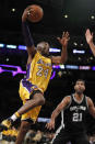 Los Angeles Lakers forward Kobe Bryant (24) goes up for a shot as San Antonio Spurs center Tim Duncan (21) watches uring the first half of an NBA basketball game in Los Angeles, Friday, Feb. 19, 2016. (AP Photo/Alex Gallardo)