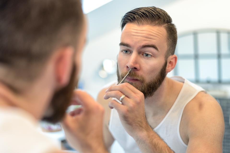 Handsome bearded young man standing plucking his nasal hairs in front of the mirror in the bathroom during his daily grooming