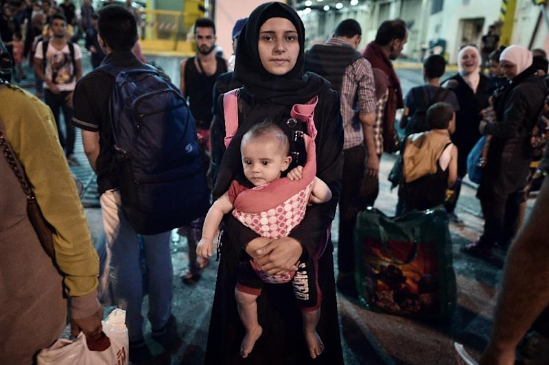 A Syrian woman carries her child as they disembark from a Greek government-chartered ferry upon arrival in the port of Piraeus on August 26, 2015 (AFP Photo/Louisa Gouliamaki)