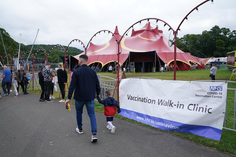 People walk past signs for the pop-up Covid-19 vaccination clinic by Circus Extreme in Halifax (Owen Humphreys/PA) (PA Wire)