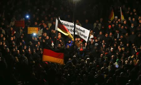 Participants hold German national flags during a demonstration called by anti-immigration group PEGIDA in Dresden