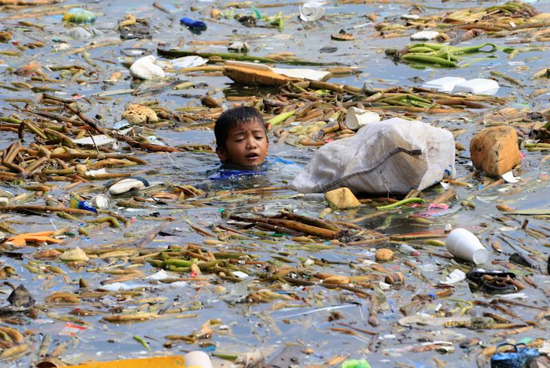 A boy swims as he collects recyclable plastic bottles drifting with garbage along the coast of Manila Bay at the slum area in the Baseco Compound in metro Manila, Philippines. (Photo: Romeo Ranoco/Reuters)
