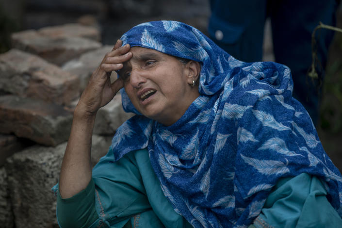 A Kashmiri villager cries beside a house that was destroyed in a gunfight in Pulwama, south of Srinagar, Indian controlled Kashmir, Wednesday, July 14, 2021. Three suspected rebels were killed in a gunfight in Indian-controlled Kashmir on Wednesday, officials said, as violence in the disputed region increased in recent weeks. Two residential houses were also destroyed. (AP Photo/ Dar Yasin)