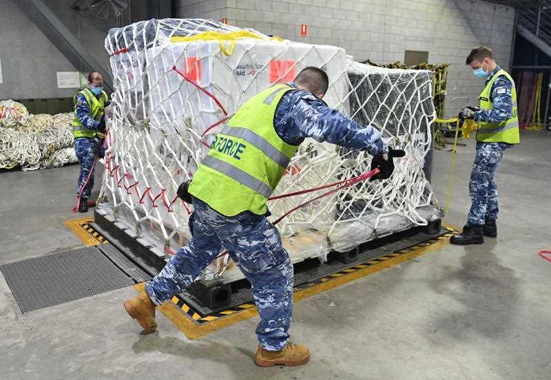 Royal Australian Air Force personal are seen preparing COVID-19 vaccines and humanitarian supplies for loading onto a C-17A Globemaster at RAAF Base Amberley, west of Brisbane.