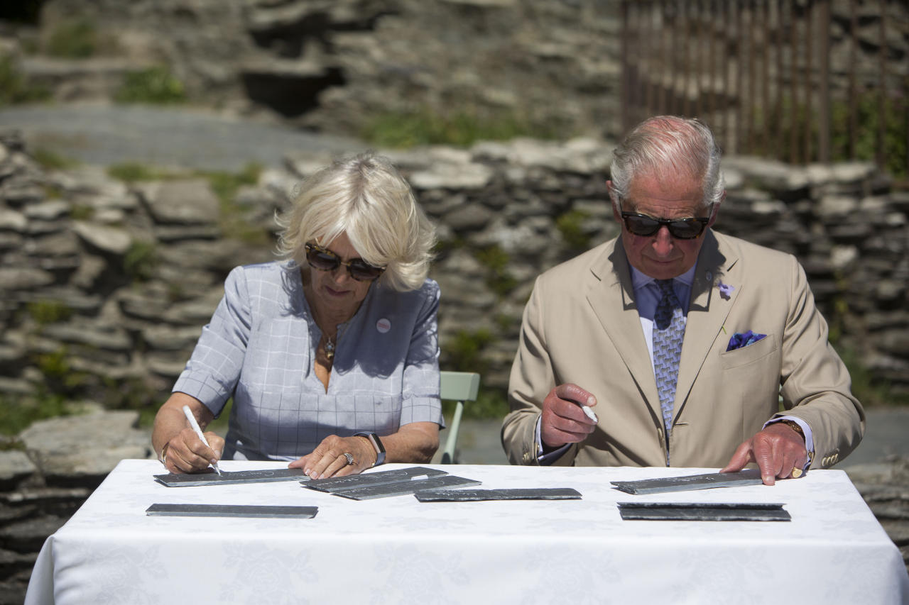 The Prince of Wales and the Duchess of Cornwall sign their names on slates that will be incorporated into Tintagel bridge during a visit to Tintagel Castle while on a three day visit to Cornwall.
