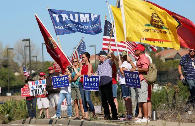 Demonstrators hold signs in support of President-elect Donald Trump outside Camp Pendleton in Oceanside, Calif., on Nov. 11, 2016. (Photo: Sandy Huffaker/Reuters)