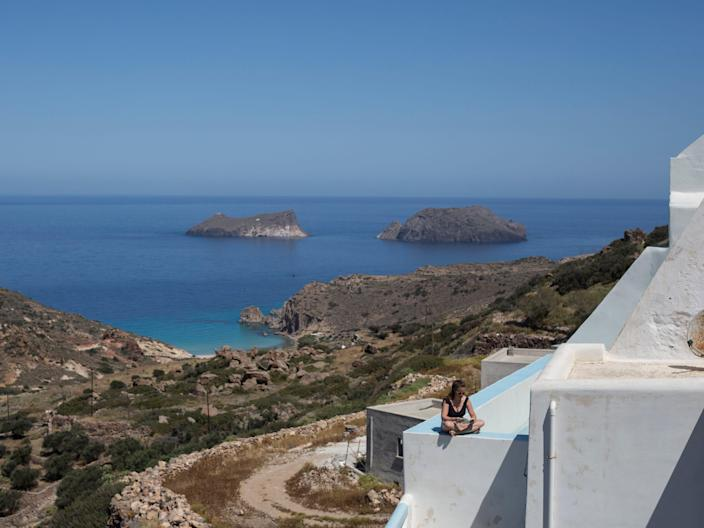 A person reading a book on a terrace overlooking blue waters in Greece