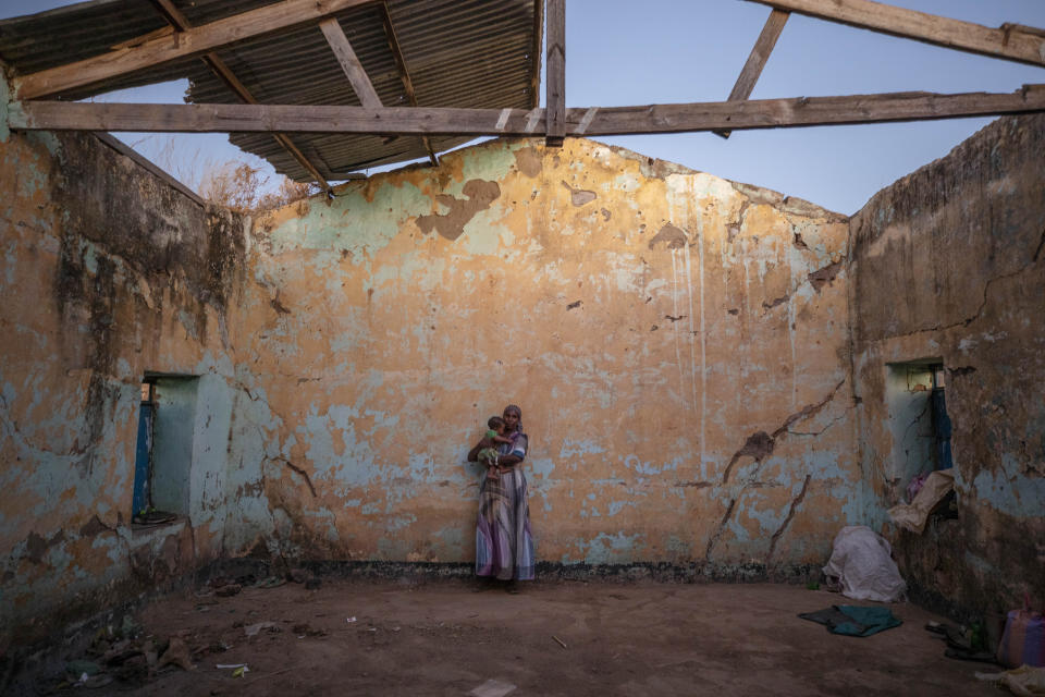 A woman who fled the conflict in Ethiopia's Tigray region holds her child inside of her temporary shelter at Umm Rakouba refugee camp in Qadarif, eastern Sudan, Monday, Dec. 7, 2020. (AP Photo/Nariman El-Mofty)