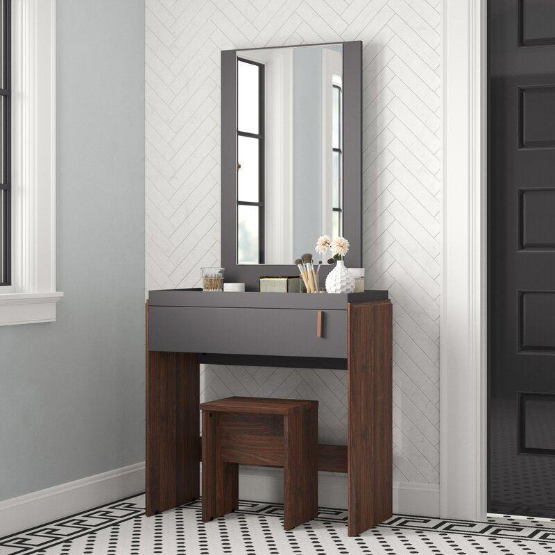 """<p><strong>Wrought Studio</strong></p><p>wayfair.com</p><p><strong>$199.99</strong></p><p><a href=""""https://go.redirectingat.com?id=74968X1596630&url=https%3A%2F%2Fwww.wayfair.com%2Ffurniture%2Fpdp%2Fwrought-studio-askern-vanity-set-with-stool-and-mirror-w001062798.html&sref=https%3A%2F%2Fwww.cosmopolitan.com%2Flifestyle%2Fg36689175%2Fbest-makeup-vanity-with-storage%2F"""" rel=""""nofollow noopener"""" target=""""_blank"""" data-ylk=""""slk:Shop Now"""" class=""""link rapid-noclick-resp"""">Shop Now</a></p><p>Well, damn. She's dark, she's moody, she's <em>sexy</em>. And best of all, she comes with a deep drawer for storing all of your serums and makeup tools.</p>"""