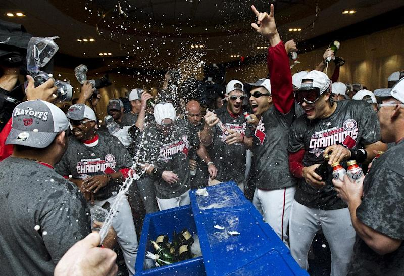 Washington Nationals general manager Mike Rizzo, center fielder Bryce Harper, starting pitcher Gio Gonzalez and left fielder Michael Morse celebrate with teammates after clinching the National League East division title following their 2-0 loss to the Philadelphia Phillies in a baseball game, Monday, Oct. 1, 2012, in Washington. (AP Photo/Manuel Balce Ceneta)