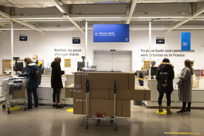 "Customers wearing face masks as a precaution against the spread of coronavirus, wait at customer services in an Ikea store on its reopening day, in Geneva, Switzerland, Monday, March 1, 2021. Swiss authorities last week gave a go-ahead to what they called a ""cautious"" reopening despite a new, more-transmissible COVID-19 variant that first appeared in Britain that is increasingly circulating in the rich Alpine country. (Salvatore Di Nolfi/Keystone via AP)"