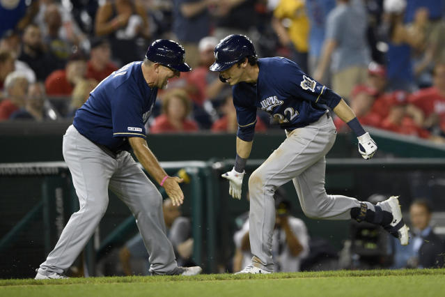 Milwaukee Brewers' Christian Yelich, right, celebrates his home run with third base coach Ed Sedar (0) during the 13th inning of a baseball game against the Washington Nationals, early Sunday, Aug. 18, 2019, in Washington. The Brewers won 15-14 in 14 innings. (AP Photo/Nick Wass)