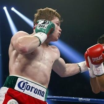 Canelo Alvarez, of Mexico, left, punches Josesito Lopez during a super welterweight championship boxing match on Saturday, Sept. 15, 2012, in Las Vegas. Alvarez won the match. (AP Photo/Isaac Brekken)