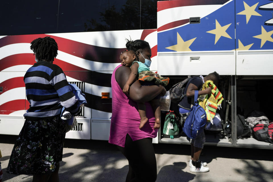 A young migrant sleeps on the shoulders of a woman as they prepare to board a bus toward Houston provided by a humanitarian organization after the migrants were released from U.S. Customs and Border Protection custody, Thursday, Sept. 23, 2021, in Del Rio, Texas. (AP Photo/Julio Cortez)